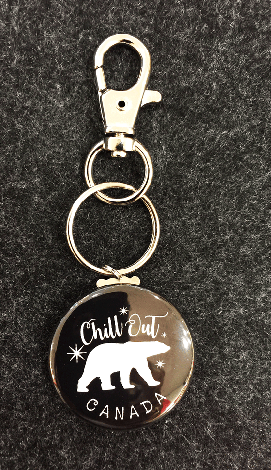"Black tab featuring a white polar bear and the words ""Chill out"" and ""CANADA"" attached to a key ring and a clasp"