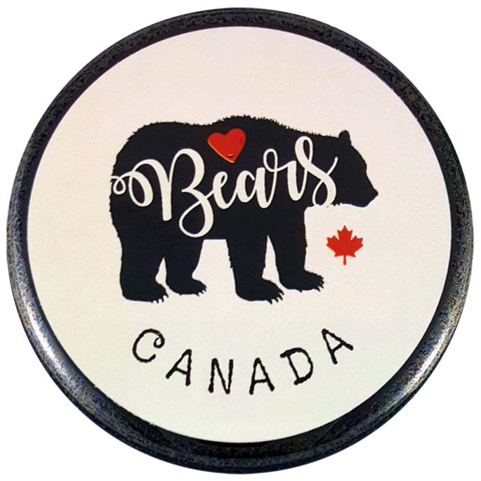 "This round magnet shows the black silhouette of a bear against a white background. The word ""bears"" has been written across the silhouette in white cursive. At the top of the silhouette is a red heart, and to its right is a red maple leaf. The word ""Canada"" is written below the bear in black text."
