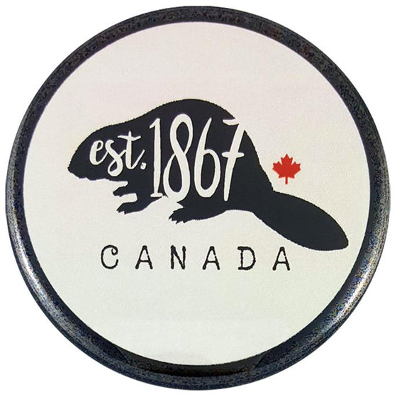 "This round magnet shows the black silhouette of a beaver against a white background. The words ""Est. 1867"" are written in white cursive across the silhouette. To the beaver's right is a small red maple leaf. The word ""Canada"" is written under the beaver in black text."