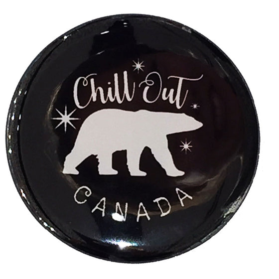 "This round magnet shows the silhouette of a white polar bear against a black background. Several small twinkling stars surround the polar bear. The words ""chill out"" are written above the bear in white cursive, and the word Canada is written below."