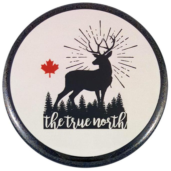"This round magnet shows the black silhouette of an antlered deer against a white background.  Black lines surrounding the deer's head suggest it is standing in front of a bright light. To the deer's left is a red maple leaf. At the deer's feet is the silhouette of an evergreen forest with the words ""the true north"" written across it."