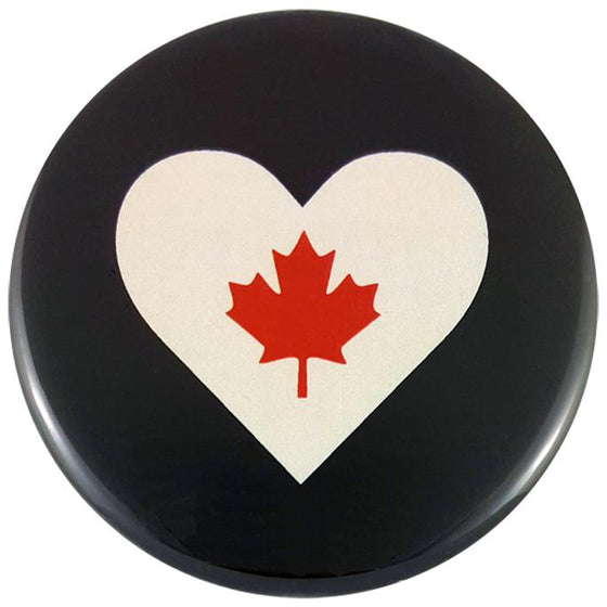 This round magnet shows a white heart against a black background. A red maple leaf is printed inside of the heart.