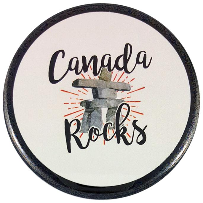 "This round magnet shows a small watercolour Inukshuk on a white background. It has a halo of red rays surrounding its body. The words ""Canada rocks"" are written in black cursive text above and below the Inukshuk."