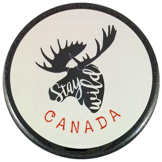 "This round magnet shows the black silhouette of a moose head against a white background.  The moose has a full rack of antlers. The words ""stay wild"" are written in white cursive inside the silhouette of the mouse. The word ""Canada"" is written in red text below the moose."