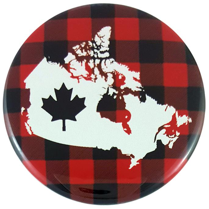 This round magnet shows the white silhouette of country of Canada against a red buffalo check background. A black maple leaf is printed over the left half of the country, partially obscuring the prairies and northwest territories.