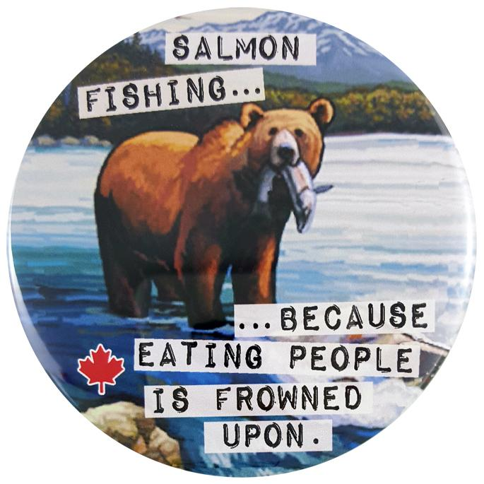 "This round magnet shows a vintage picture of a grizzly bear at the top of a water fall. A salmon hangs from its mouth. Across the picture the words ""salmon fishing…because eating people is frowned upon"" are printed in black text against a white stripe. The text resembles a classic typewriter font."