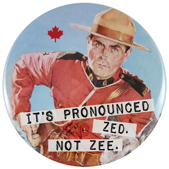 "This round magnet shows a vintage picture of a Canadian Mounty. He is leaning to the right and appears to be pulling something out from his pocket. Across the bottom of the picture the words ""it's pronounced zed, not zee"" are printed in black text against a white stripe. The text resembles a classic typewriter font."