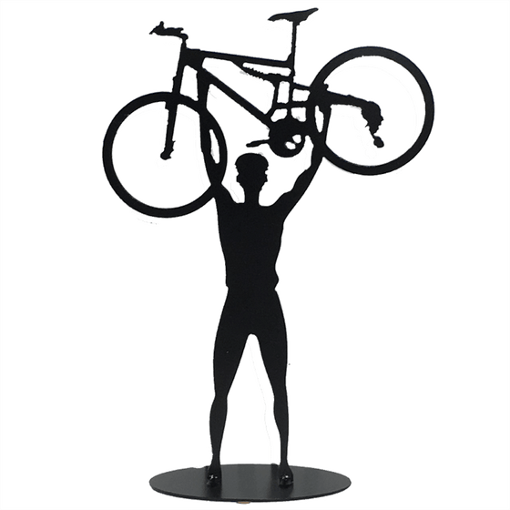 This metal sculpture shows the matte black silhouette a male cyclist facing the viewer. He holds a mountain bike triumphantly above his head. The bike design is slightly simplified, and the wheels have no spokes. The piece stands on a small oval base.