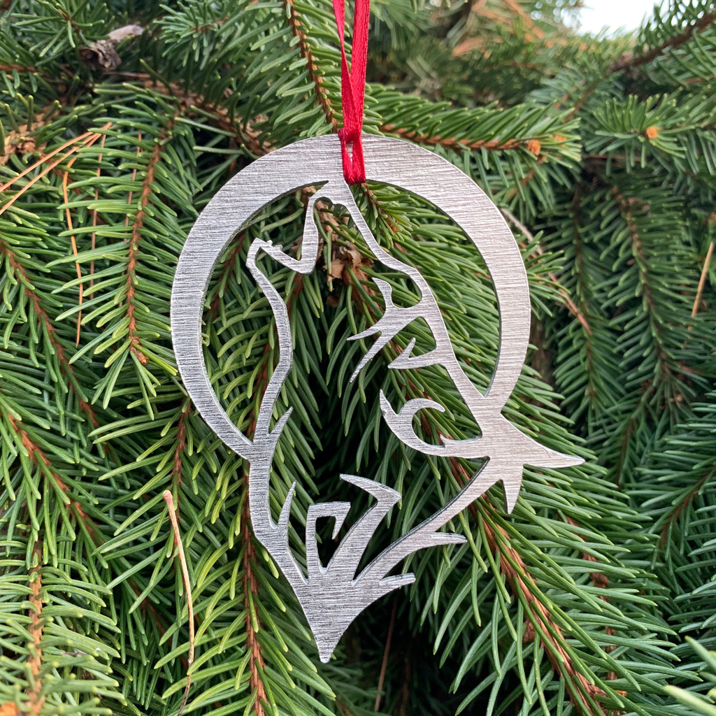 The wolf ornament with a red ribbon attached and hanging on a pine tree.