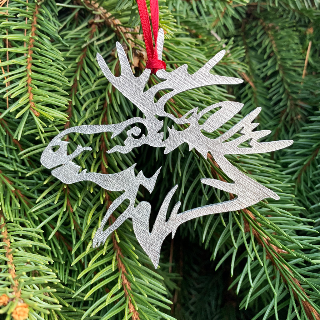 The moose ornament  with a red ribbon attached and hanging from a pine tree.