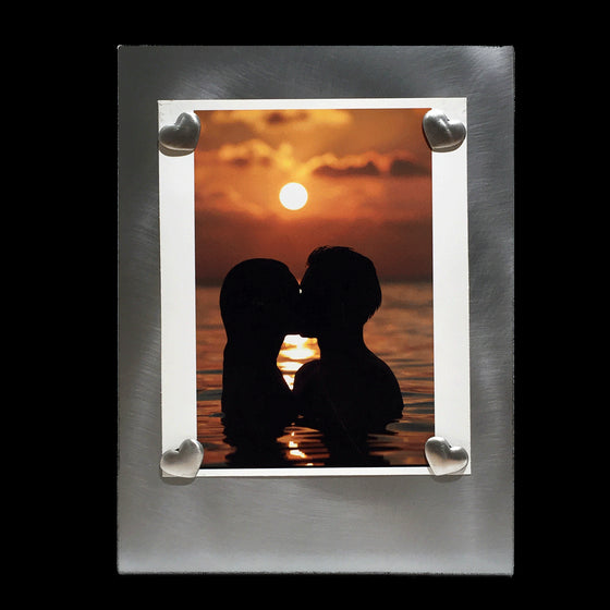 A vertical rectangular metal picture frame with four heart shaped pewter magnets holding a picture of two people swimming at sunset.