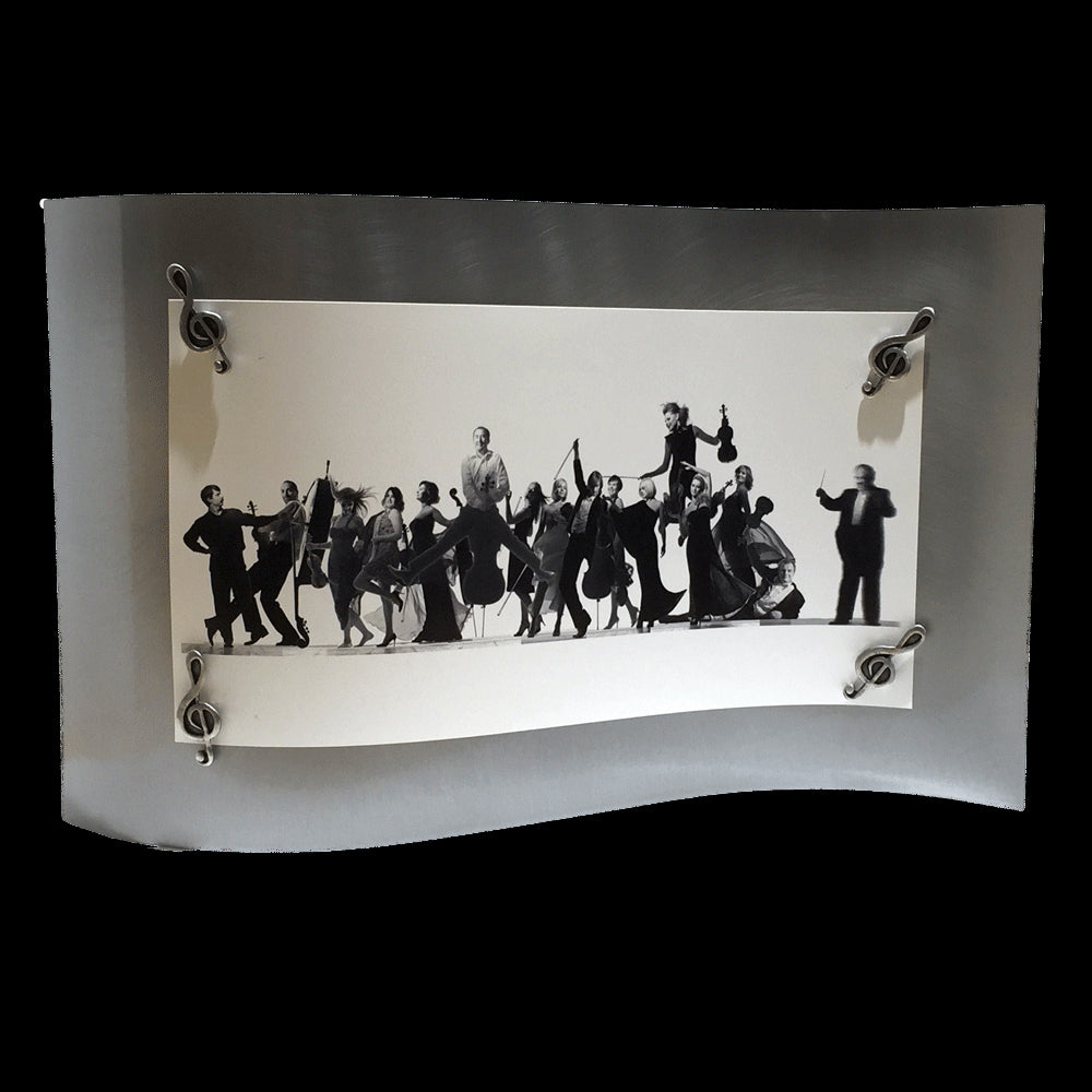 This frame consists of a single rectangular sheet of brushed steel, bent in a wave pattern so the single sheet stands on its own. A group photo of members of an orchestra is held on by four magnets in the shape of treble clefs.