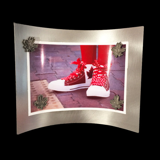 A metal rectangle, curved so it stands without additional pieces supporting it. A photo of someone red and white Canadian flag shoes is held on by four maple leaf shaped pewter magnets.
