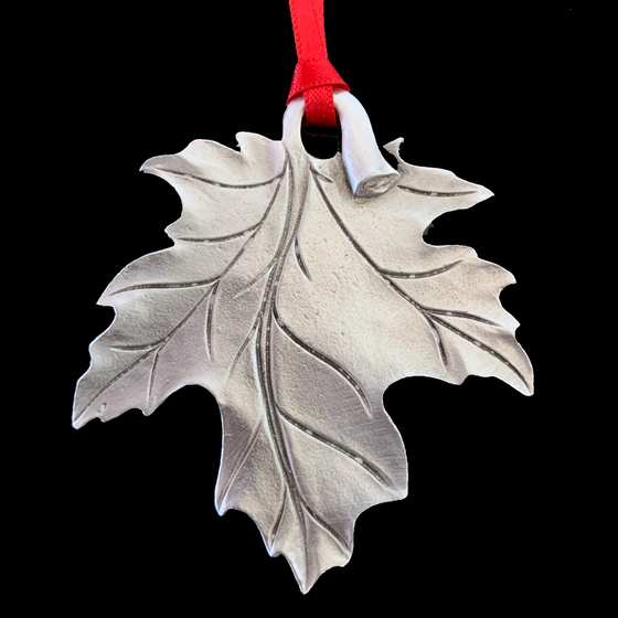 A maple leaf hangs upside down, its stem creating a loop for a red ribbon to be attached.