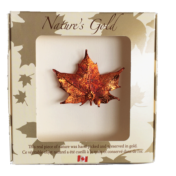 "A small metal coated maple leaf sits in a paper box. The metal has an iridescent finish, and sparkles in several shades of orange and red. The top face of the box has a wide square viewing hole. The box is tan with gold maple leaf prints. At the top of the box is written Nature's Gold. At the bottom is written ""this real piece of nature was handpicked and preserved in gold"" followed by ""Ce véritable objet naturel a été cueilli à la main et conservé dans de l'or"""