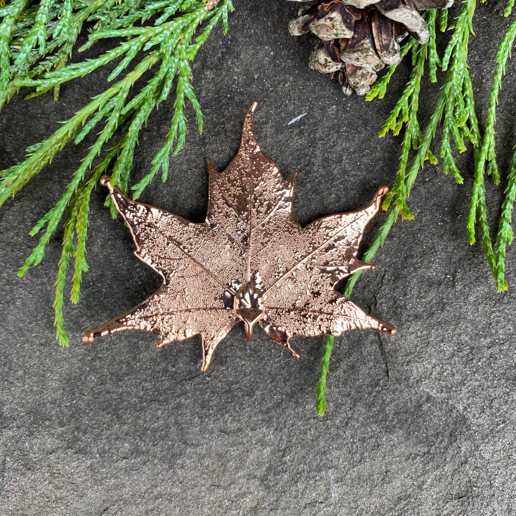 A small copper coated maple leaf sits on a stone background. The copper has a bright finish. At the top of the picture are decorative evergreen leaves and a pine cone.