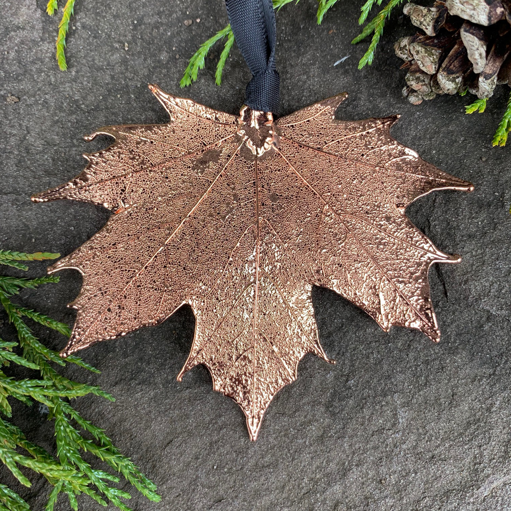 A large copper coated maple leaf sits on a stone background. A black ribbon is tied to the stem end of the leaf. The copper has a bright finish. Around the picture are decorative evergreen leaves and a pinecone.