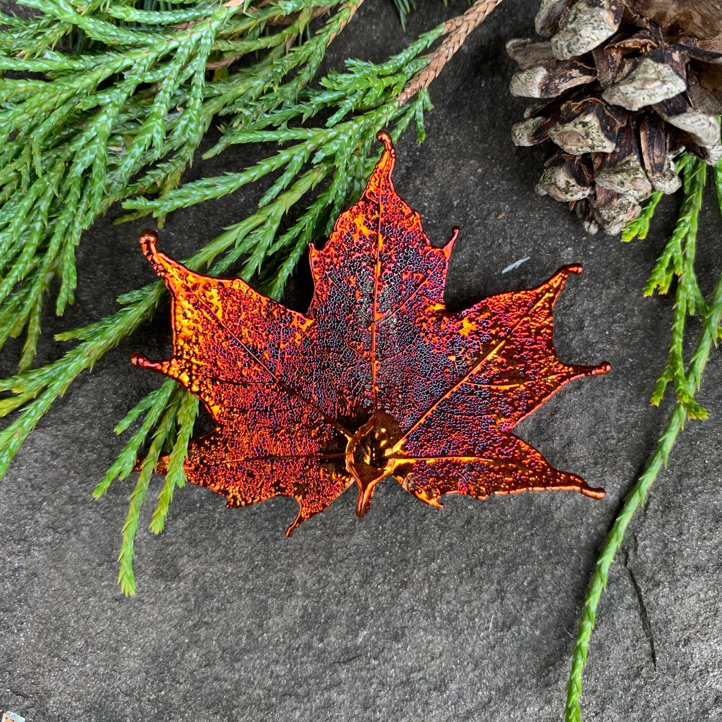 A small metal coated maple leaf sits on a stone background. The metal has an iridescent finish and sparkles in several shades of orange and red. At the top of the picture are decorative evergreen leaves and a pine cone.