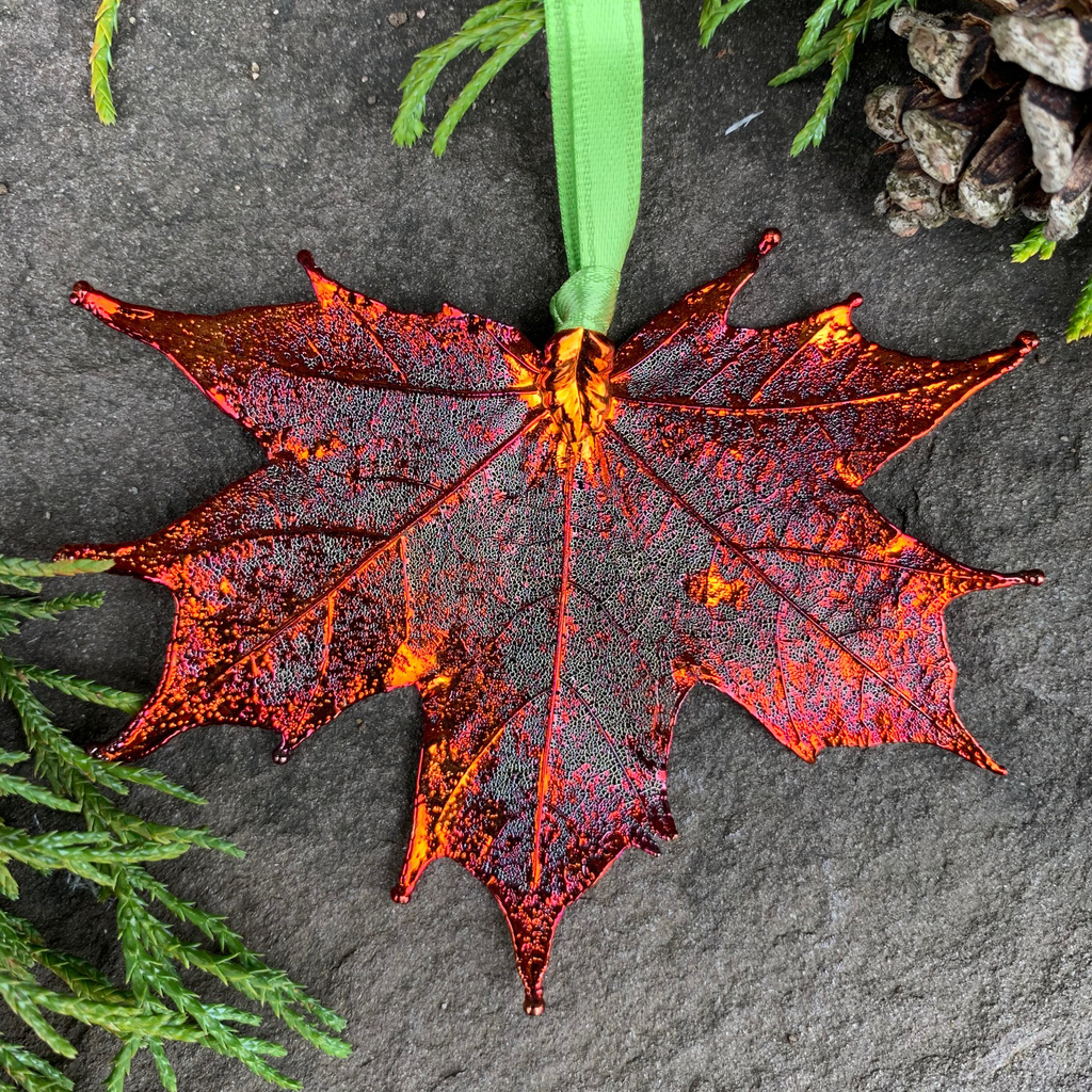 A large metal coated maple leaf sits on a stone background. The metal has an iridescent finish, and sparkles in several shades of orange and red. A green ribbon is attached to the stem end of the leaf.  Around the picture are decorative evergreen leaves and a pine cone.