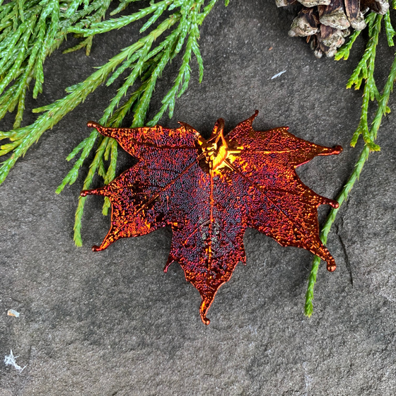 A small metal coated maple leaf sits on a stone background. The metal has an iridescent finish, and sparkles in several shades of orange and red. At the top of the picture are decorative evergreen leaves and a pine cone.