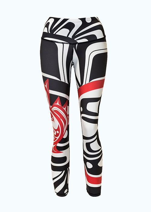 These black, white and red leggings are decorated with a Haida eagle and maple leaf motif. The motif shows an eagle with one wing outstretched in front of it. It is enclosed by a red circle, which is itself enclosed by a maple leaf. A small version of this motif is on the right leg, while a larger version begins on the left leg and spreads across the entire leggings.