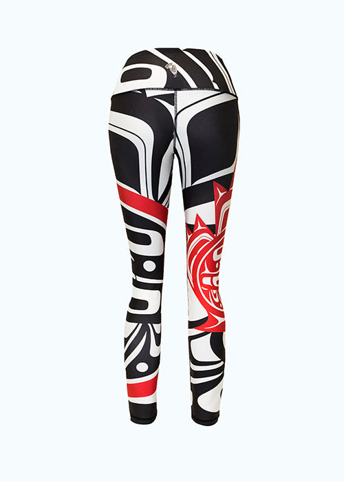 The eagle maple leaf leggings viewed from behind. Again, the large and small motifs can be seen. The white form lines of the larger motif contrast with the black background.