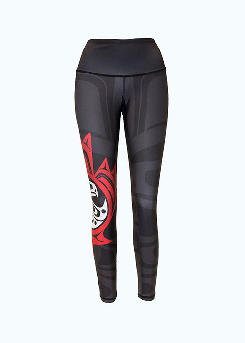These black, grey, red and white leggings are decorated with a Haida eagle and maple leaf motif. The motif shows an eagle with one wing outstretched in front of it. It is enclosed by a red circle, which is itself enclosed by a maple leaf. A small red and white version of this motif is on the right leg. A larger grey version begins on the left leg and spreads across the entire leggings, though it is difficult to see against the black background.
