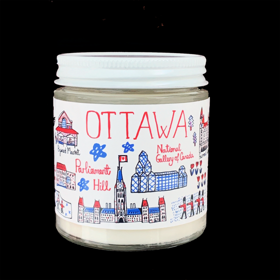 "A white candle in a glass jar with a screw top lid. The jar's label reads ""Ottawa"" and is covered in an array of cartoonishly drawn Ottawa landmarks in red, blue and black on a white background. Notable landmarks include Parliament Hill, the Byward market, the Fairmont Chateau Laurier, and the national gallery of art. The simple line art and colour palate give this candle a bright, fun feeling."