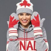 A smiling woman wearing a pullover, maple leaf mittens, and a toque. She is holding her hands up beside her head to show off the back of the mittens. The mittens are grey knitted cotton with a white and red wrist warmer. Each mitten has half of a red maple leaf sewn into it. Holding the mitten side by side would complete the maple leaf image.