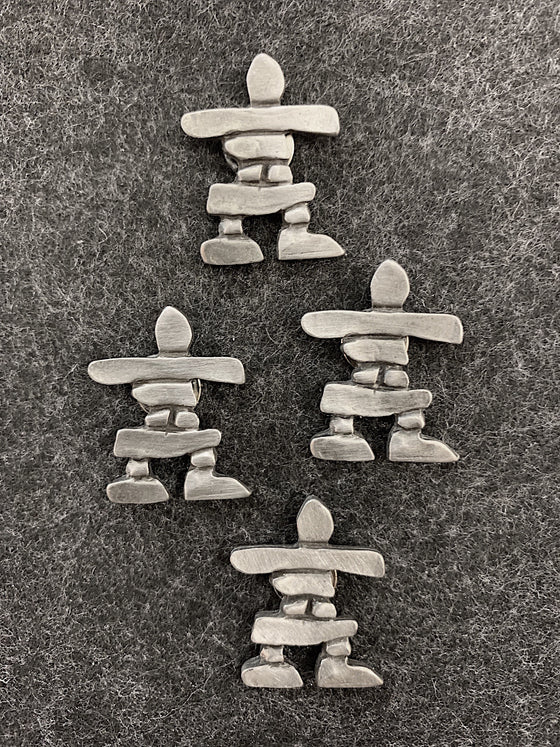 Four pewter magnets in the shape of inukshuks.