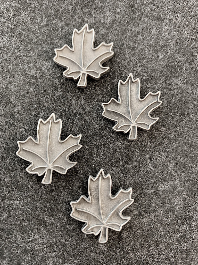 Four pewter magnets in the shape of maple leaves. Raised lines outline the outside of the leaf, and veins to the five points of the leaf.