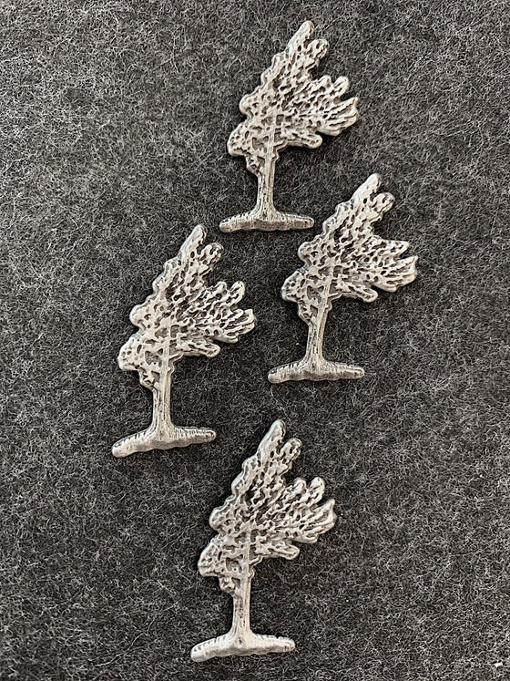 Four pewter magnets in the shape of windswept pine trees.
