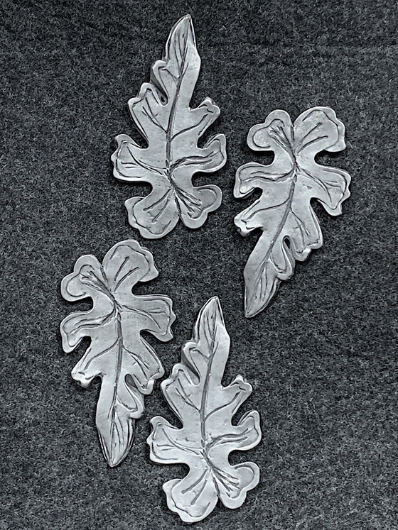 Four pewter magnets in the shape of oak leaves.