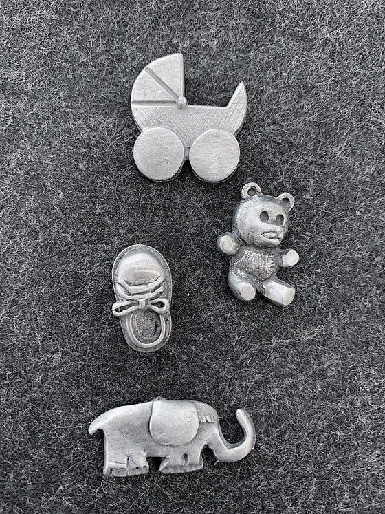 This set of four magnets includes a 1960's style baby carriage, a teddy bear, a baby shoe, and an elephant.