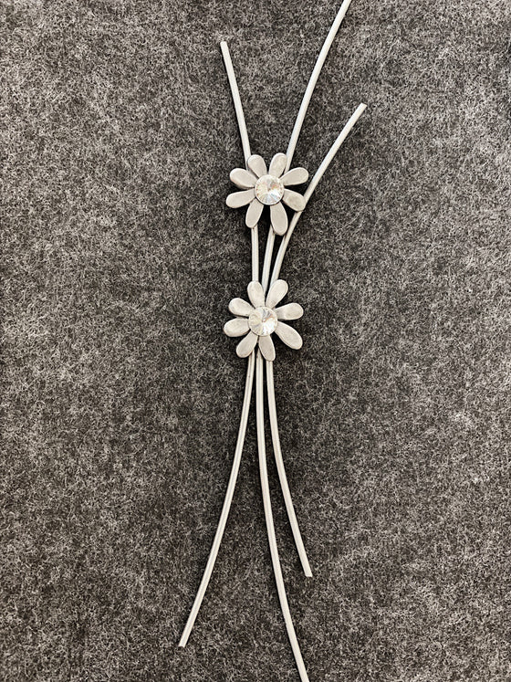 Three curved pewter rods meet in the middle with two pewter flowers with glass centers sitting on top.