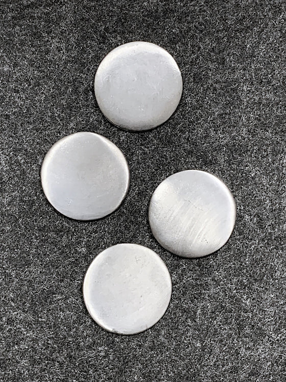 Four plain circular pewter magnets.