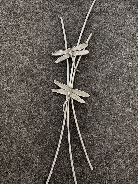 Three curved pewter rods meet in the middle with two pewter dragonflies sitting on top.