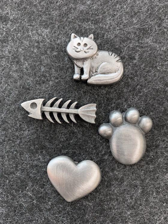 This set of four pewter magnets includes a striped cat, a paw print, a heart, and a fish bone.