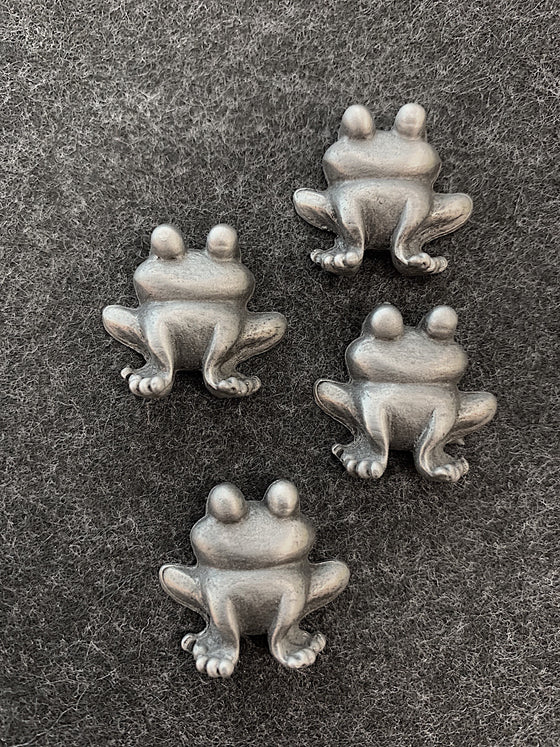 four pewter magnets in the shape of frogs facing forward with large cartoonish eyes on the tops of their heads.