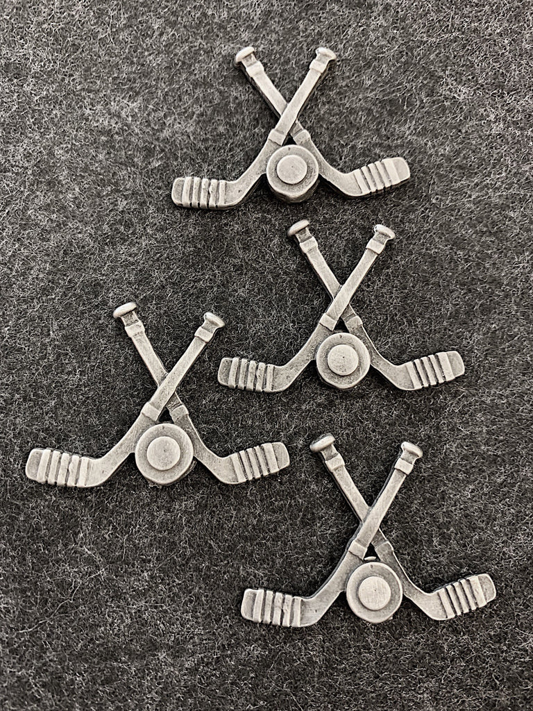 Four pewter magnets in the shape of two hockey sticks crossed with a puck between them.