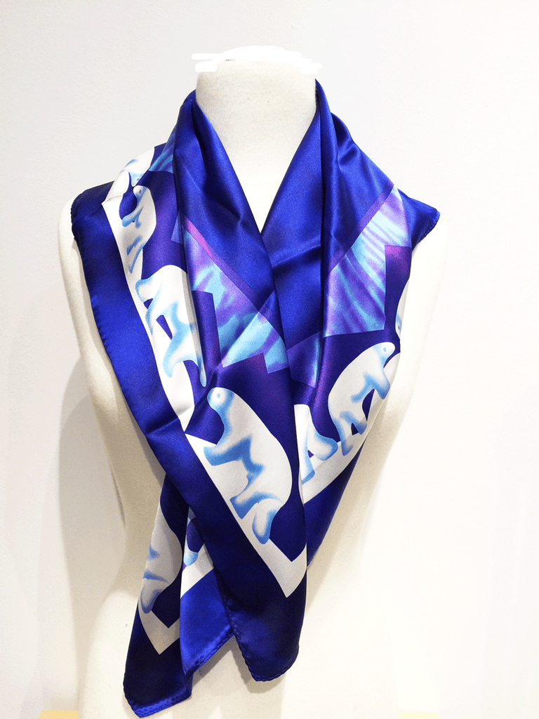 Pictured here is a royal blue silk scarf with light blue and white accents. Featured on the scarf is the majestic Canadian polarbear.