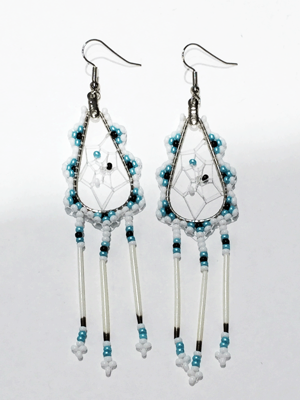 A pair of porcupine quill earrings. The hanging earrings are a tear drop shape hoop with dream catcher style weaving on the inside with white, black, and turquoise beads in the center. Turquoise, black, and white beads are woven along the outside of the hoop and hanging off of the bottom are three strands with white, turquoise, and black beads, then a piece of porcupine quill, with more white and turquoise beads at the end.