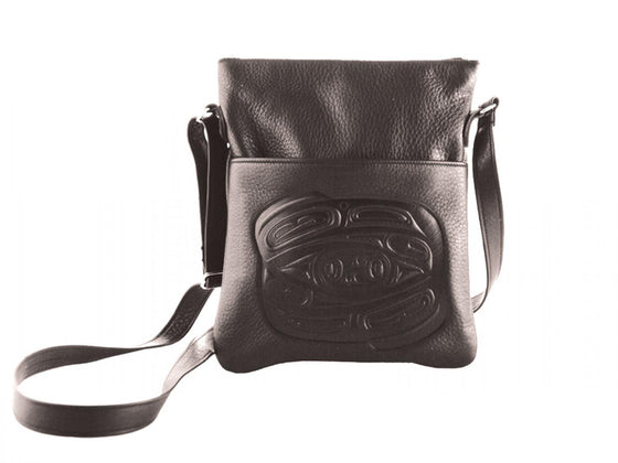 A black deerskin shoulder bag with a Haida style raven embossed onto the front. An adjustable black shoulder strap is attached to either end of the bag.