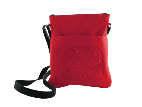 A red deerskin shoulder bag with a Haida style raven embossed onto the front. An adjustable black shoulder strap is attached to either end of the bag.