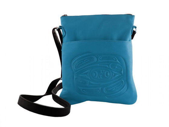 A turquoise deerskin shoulder bag with a Haida style raven embossed onto the front. An adjustable black shoulder strap is attached to either end of the bag.