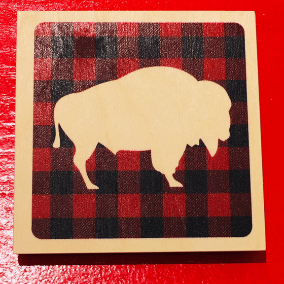 This wooden coaster features a cream coloured silhouette of a bison on a red and black buffalo check background. The coaster also has a cream coloured border.
