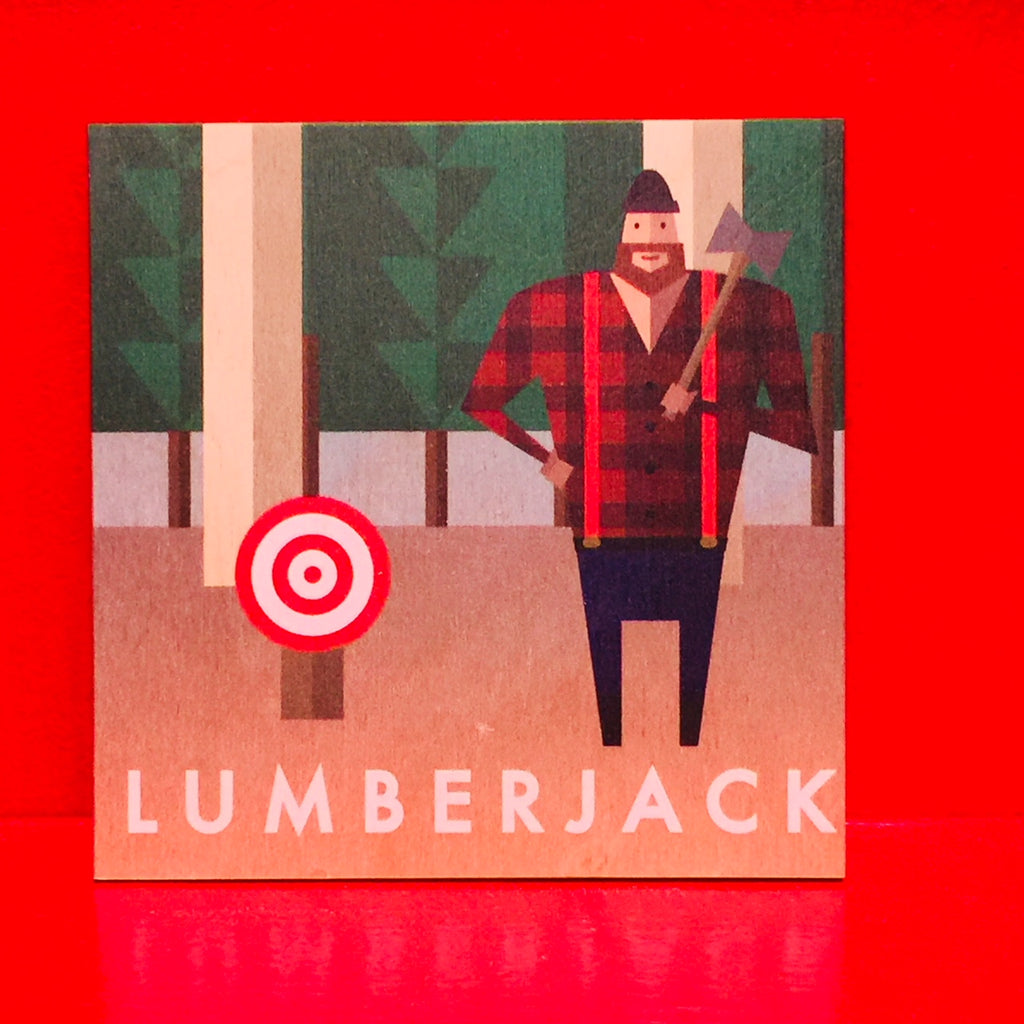 This wooden coaster features a print of a lumberjack standing in a clearing in a pine forest. The lumberjack is wearing a black toque, a buffalo check shirt, suspenders and blue pants. He is holding an axe. To his left is a red and white bullseye target, presumably for axe throwing. The word lumberjack is written at the bottom of the coaster in white text.