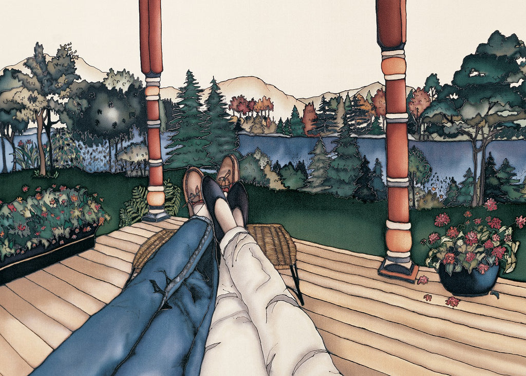 This rectangular magnet shows two pairs of legs with their feet resting on a stool as if two people are reclining next to each other. They are resting on a wooden deck by a river. The picture is richly coloured.