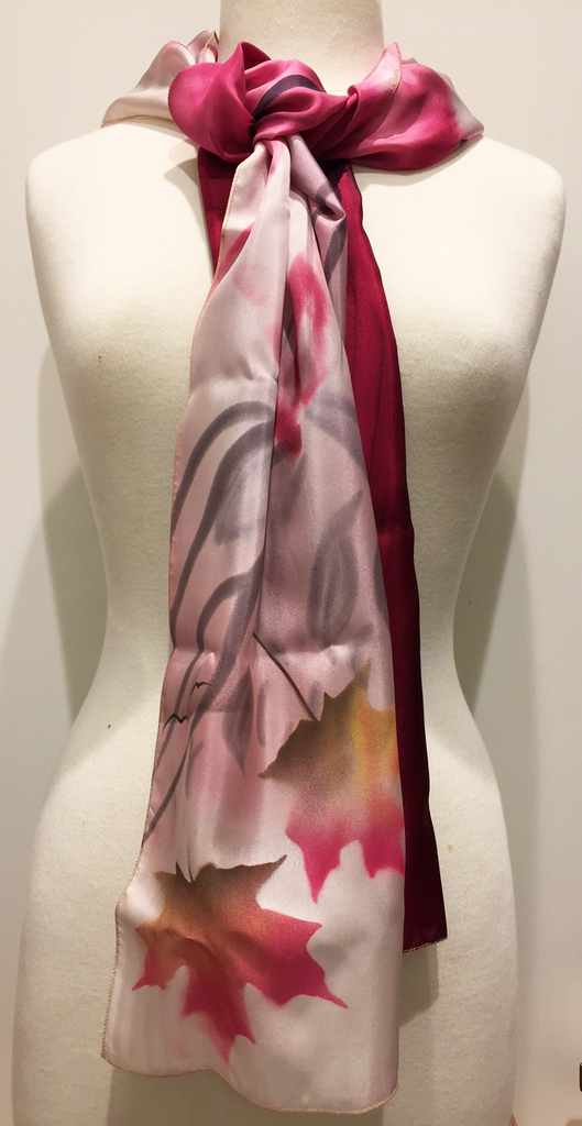 Pictured here is a deep pink/light pink/ivory hand-painted silk scarf featuring several Canadian maple leaves of various sizes.