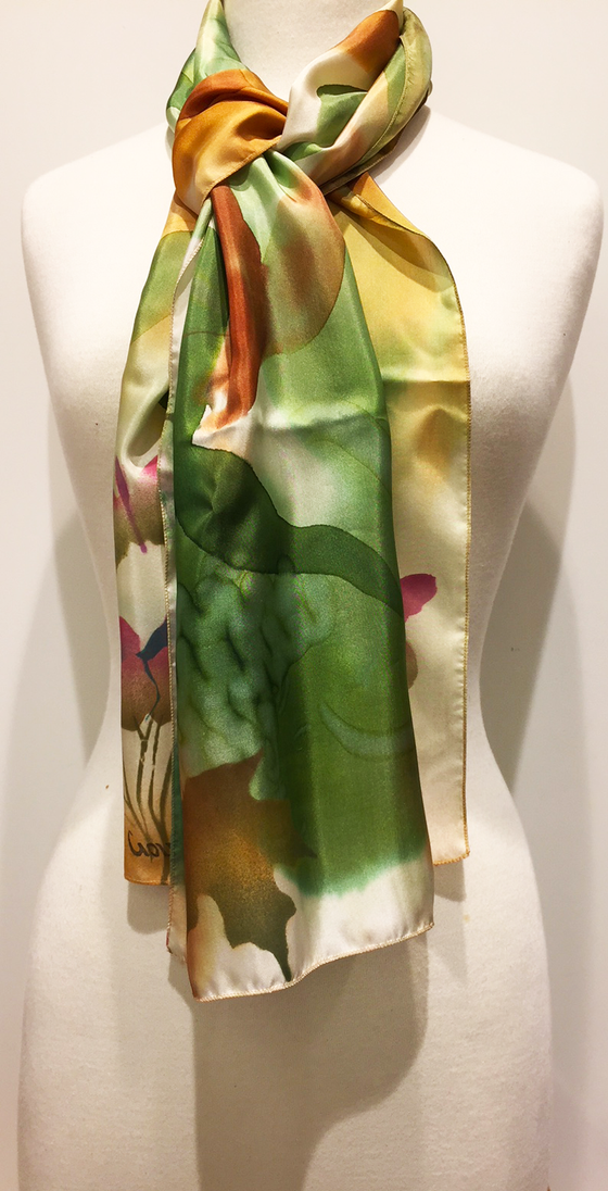 Pictured here is a green/gold/rust hand-painted silk scarf featuring several Canadian maple leaves of various sizes.